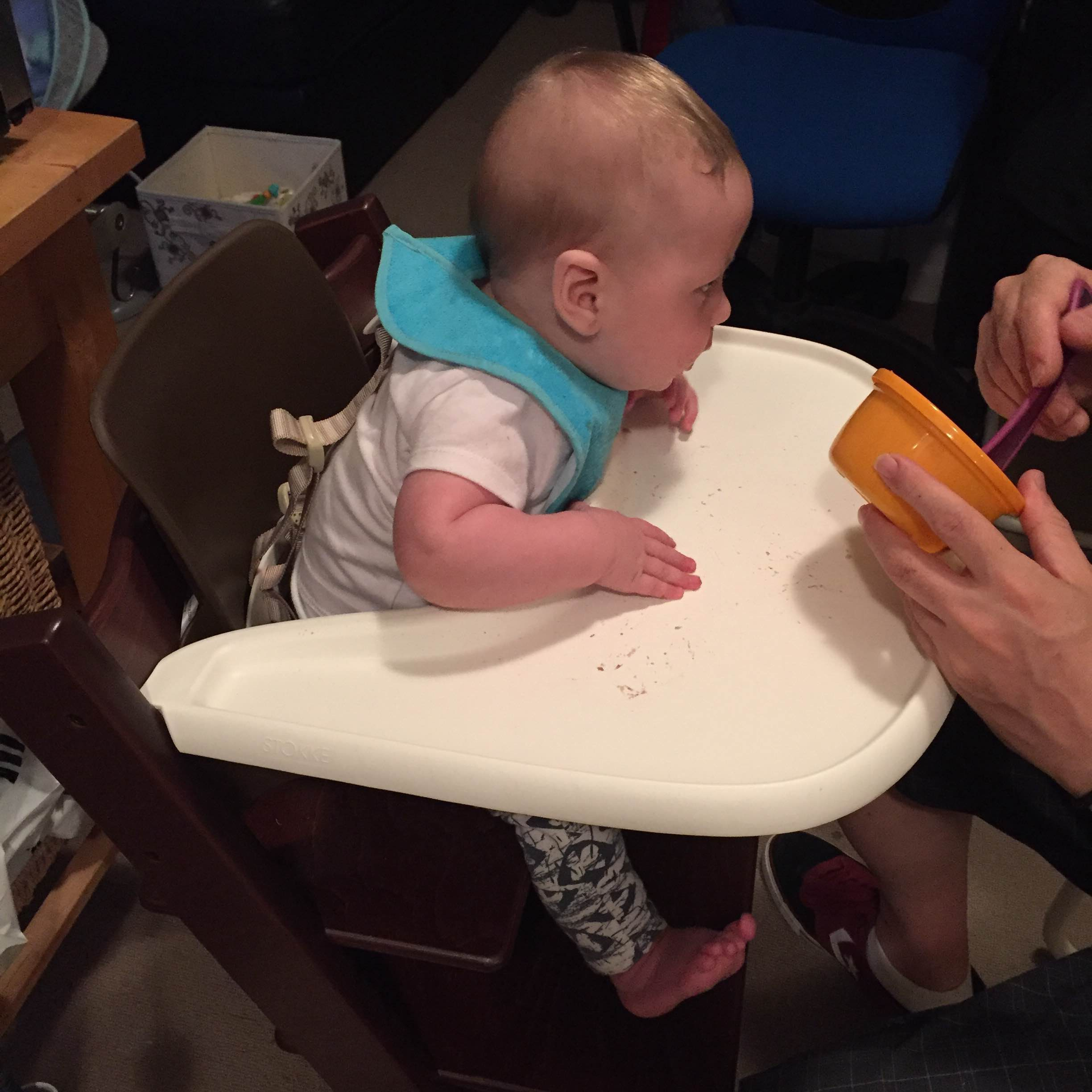Seb eating at high chair